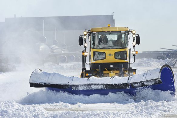 Snow plows trying to clear an airport's runways.