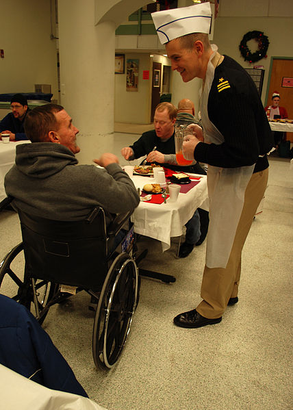 Lt. Cmdr. Anthony Savage chats with a veteran at the New England Center for Homeless Veterans during a Christmas dinner visit.