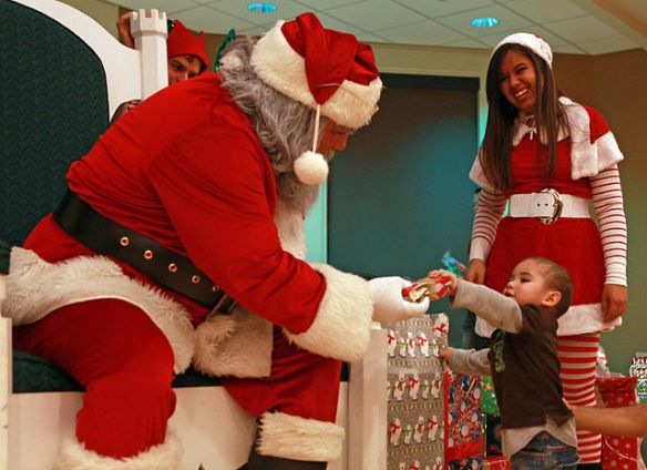 A child gives Santa a gift during an annual party.
