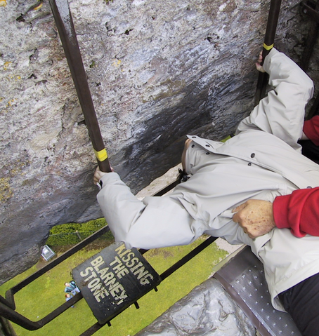 A woman leans backwards to kiss the Blarney Stone.
